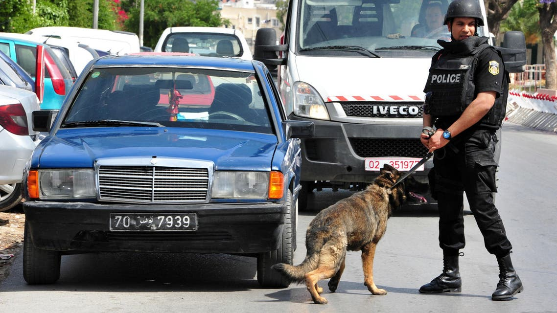 A police officer with his dog patrols near the scene of a shooting at the Bouchoucha barrack in Tunis, Tunisia, Monday May 25, 2015. A Tunisian soldier opened fire on fellow troops at a military barrack in the capital Monday, killing seven people and injuring ten, before he was himself killed, a spokesman for Tunisia's Defense Ministry said. (AP Photo/Ali Dali)