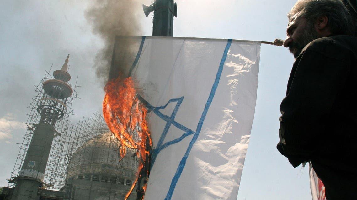 Iranian protestors burn a representation of an Israeli flag in an anti-Israeli rally at the Felestin (Palestine) Sq. in Tehran, Iran, Friday, July 7, 2006.
