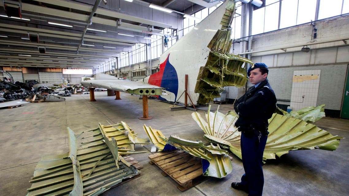 Dutch military police stand next to parts of the wreckage of the Malaysia Airlines Flight 17, displayed in a hangar at Gilze-Rijen airbase, Netherlands, Tuesday, March 3, 2015. AP