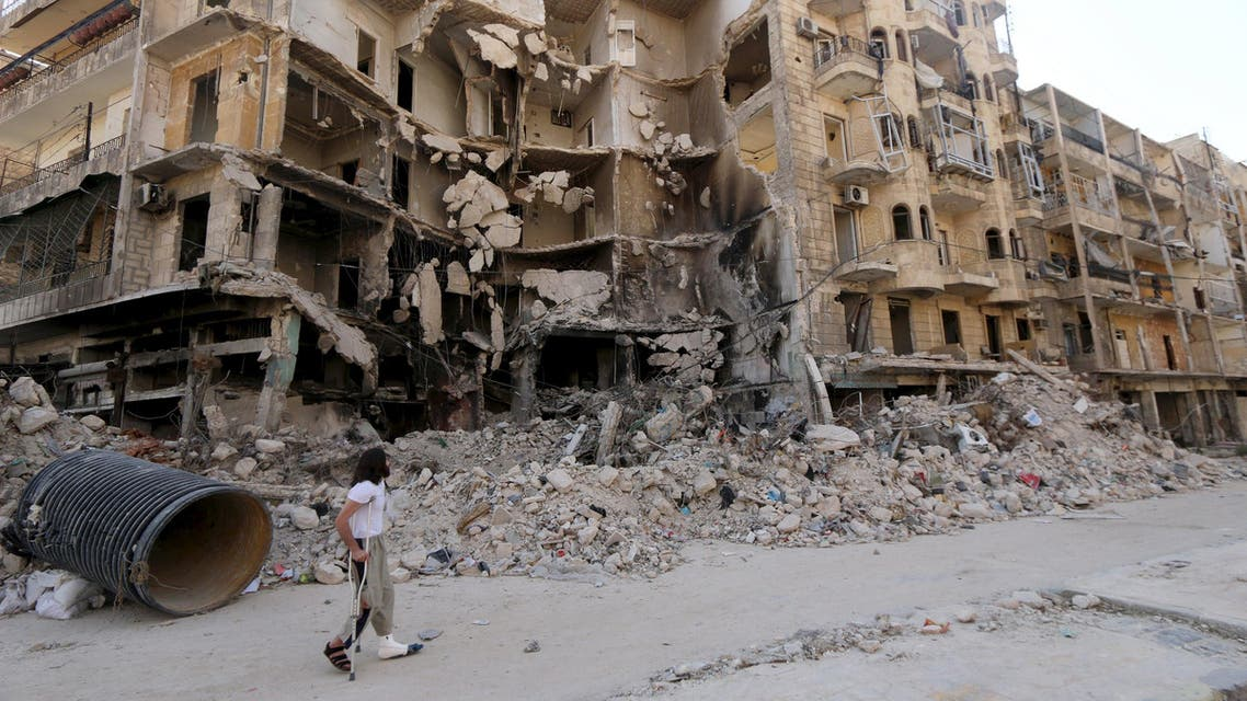 A man walks with the aid of a crutch past damaged buildings in the old city of Aleppo June 27, 2015. REUTERS
