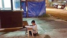 Viral photo of Filipino boy studying on the street gets him scholarship