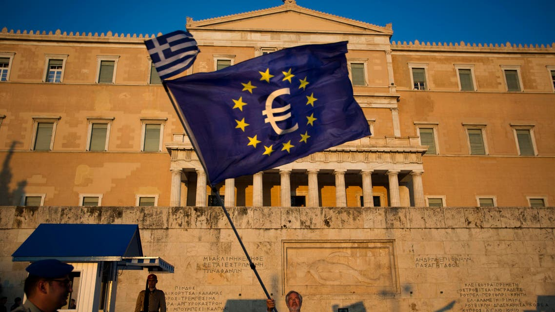 A demonstrator waves a European Union flag in front of the Greek Parliament during a rally in Athens, Thursday, July 9, 2015. Hopes that Greece can get a rescue deal that will prevent a catastrophic exit from the euro rose on Thursday, after key creditors said they were open to discussing how to ease the country's debt load, a long-time sticking point in their talks. (AP Photo/Emilio Morenatti)