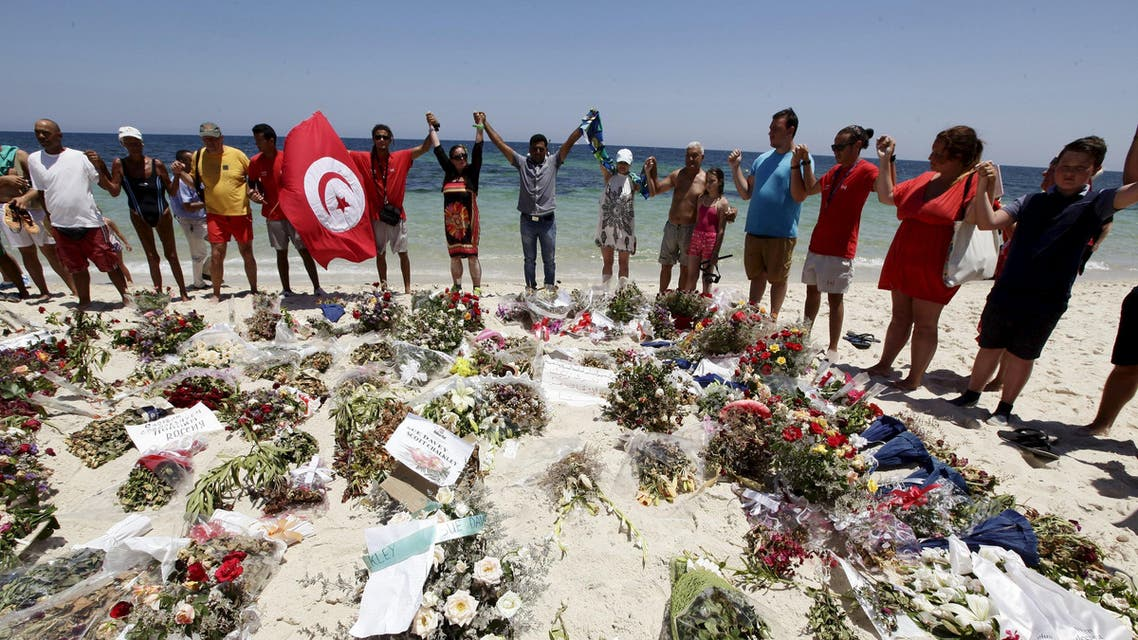 People join hands as they observe a minute's silence in memory of those killed in a recent attack by an Islamist gunman, at a beach in Sousse, Tunisia July 3, 2015. REUTERS