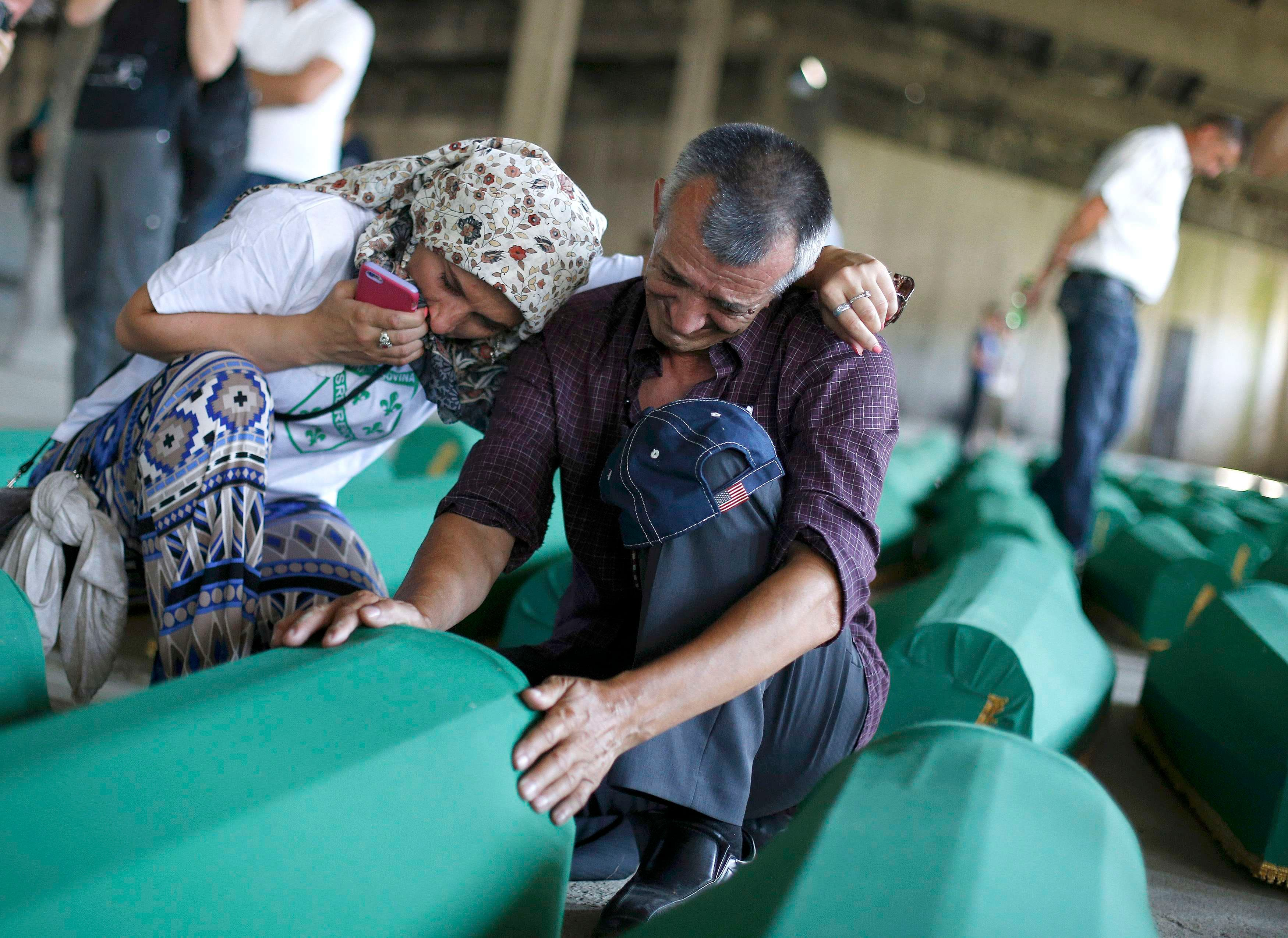 A man and a woman cry near coffins of newly identified victims of the 1995 Srebrenica massacre at the Memorial Center in Potocari near Srebrenica, Bosnia and Herzegovina, July 10, 2015. (Reuters)