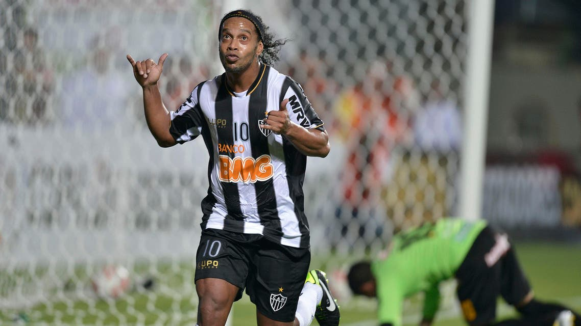 FILE - In this March 7, 2013 file photo, Brazil's Atletico Mineiro's Ronaldinho celebrates after scoring against Bolivia's The Strongest during a Copa Libertadores soccer match in Belo Horizonte, Brazil. Former Brazil star Ronaldinho remains one of the main attractions in the league, and for the third year in a row the 34-year-old playmaker will try to lead Atletico Mineiro to its first league title since 1971. Teammate Jo is one of the few league players who will be playing in the World Cup, along with Fred, the Fluminense striker who is set to start for Brazil. (AP Photo/Pedro Vilela, File)