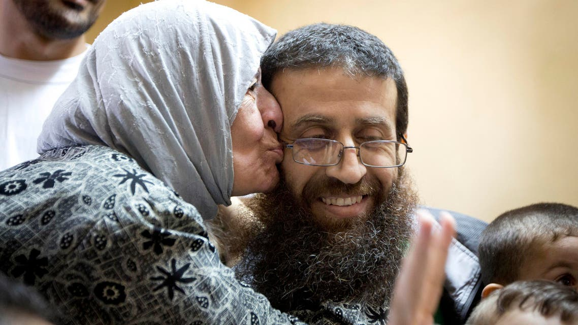 Palestinian Khader Adnan is greeted by Palestinians after his release from an Israeli prison in the West Bank village of Arrabeh near Jenin, Sunday, July 12, 2015