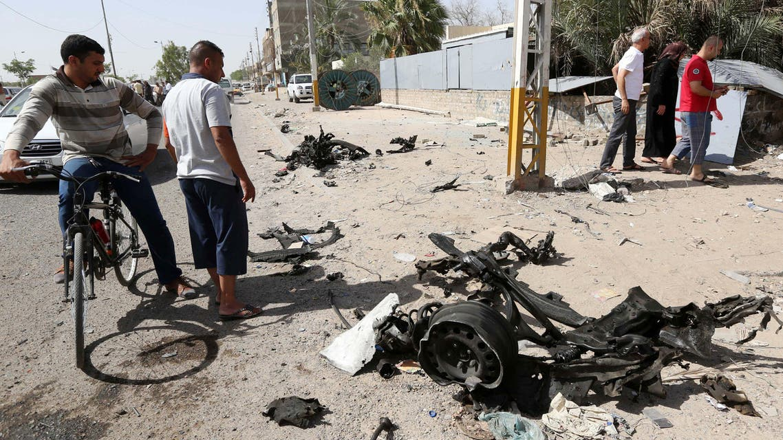 Civilians inspect the site of a car bomb attack in Baghdad's northern neighborhood of Shaab, Iraq, Thursday, June 25, 2015. AP