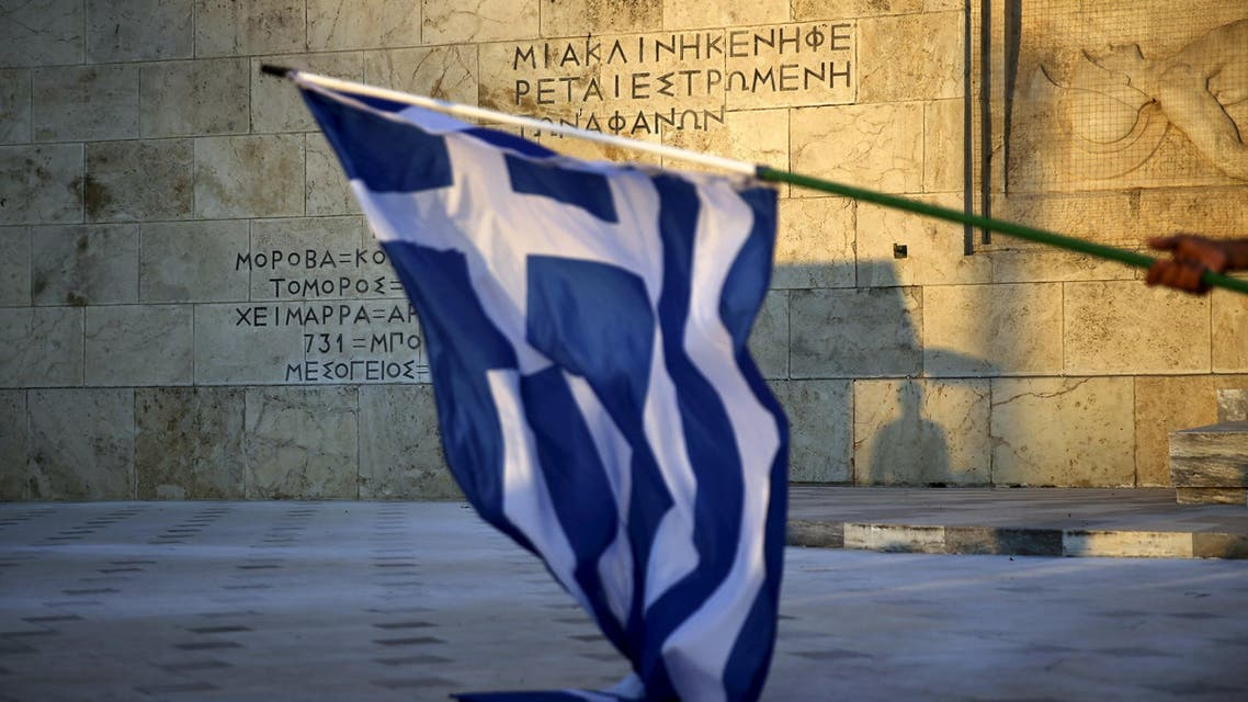 A pro-Euro protester lays a Greek national flag on the Tomb of the Unknown Soldier as a Presidential Guard is silhouetted in the background during a rally in front of the parliament building in Athens, Greece, July 9, 2015. (Reuters)