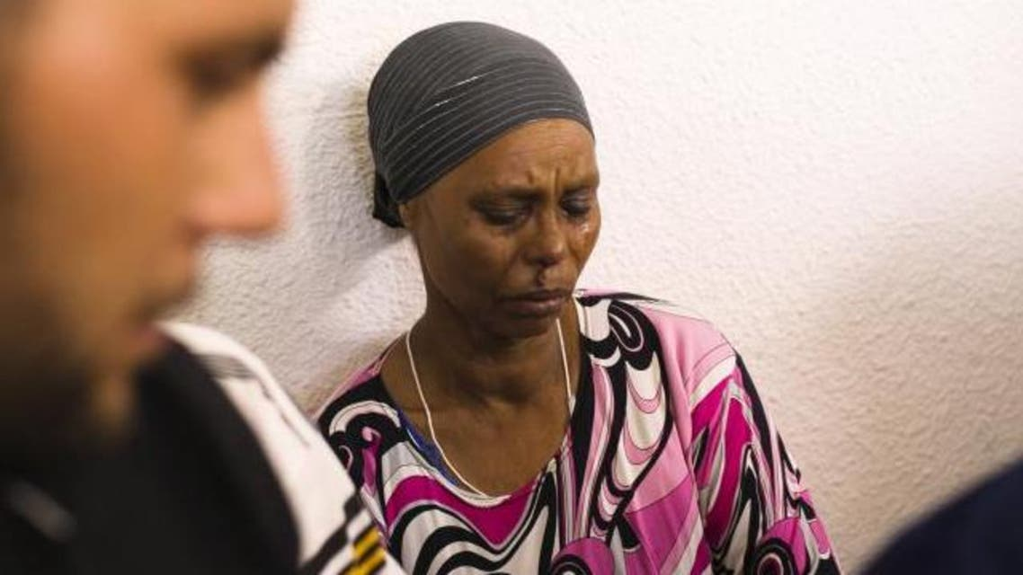 The mother of Avraham Mangisto cries outside their home in the southern city of Ashkelon, Israel July 9, 2015. (Reuters)