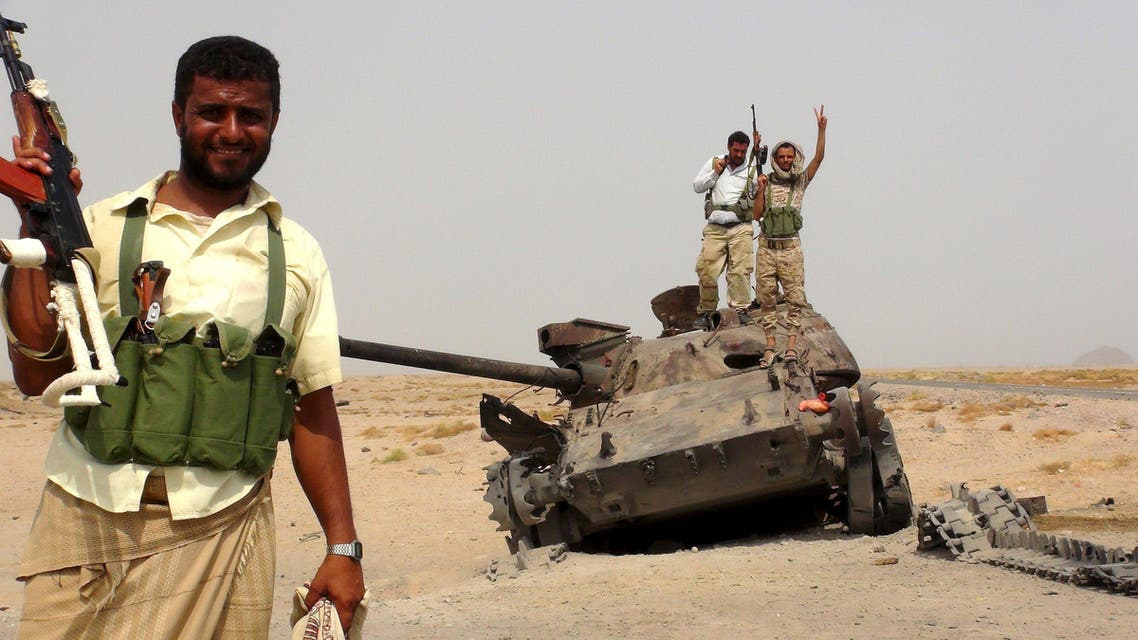 Southern Resistance fighters stand with a tank destroyed during fighting against Houthi fighters in the Emran outskirts of Yemen's southern port city of Aden. (Reuters)