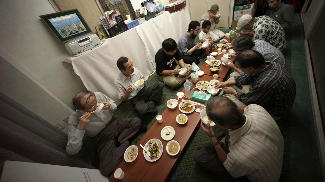 """In this July 11, 2015, photo, Muslim men break their fast with chopsticks as they eat """"Gyudon"""", or Japanese beef bowl, at the Japan Muslim Association in Tokyo. AP"""
