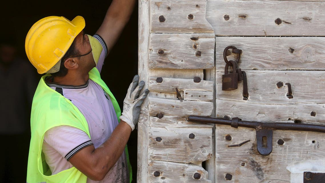 """A worker inspects a door of the 14th-century Othello Tower in Famagusta, Cyprus, June 17, 2015. The 14th-century Cypriot tower that is the fictional setting of Shakespeare's play """"Othello"""" reopens next month after undergoing renovation following decades of decay on the internationally isolated Turkish side of the ethnically divided island. REUTERS/Yiannis Kourtoglou"""