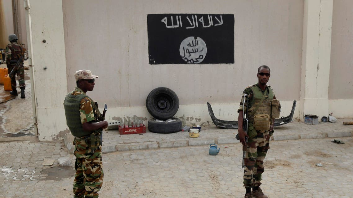 Chadian soldiers stand at a checkpoint in front of a Boko Haram flag the Nigerian city of Damasak, Nigeria, Wednesday March 18, 2015.