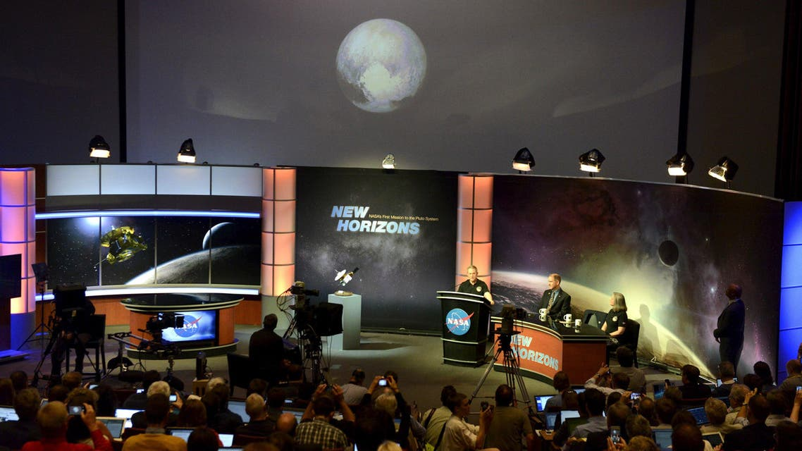 Members of the media view an image of Pluto on the screen taken a day earlier by the spacecraft New Horizons as it approached a flyby of Pluto, at NASA's Johns Hopkins Applied Physics Laboratory in Laurel, Maryland, July 14, 2015. reuters
