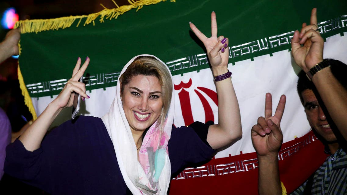 An Iranian woman shows the victory sign as people celebrate on a street following a landmark nuclear deal, in Tehran, Iran, Tuesday, July 14, 2015. AP