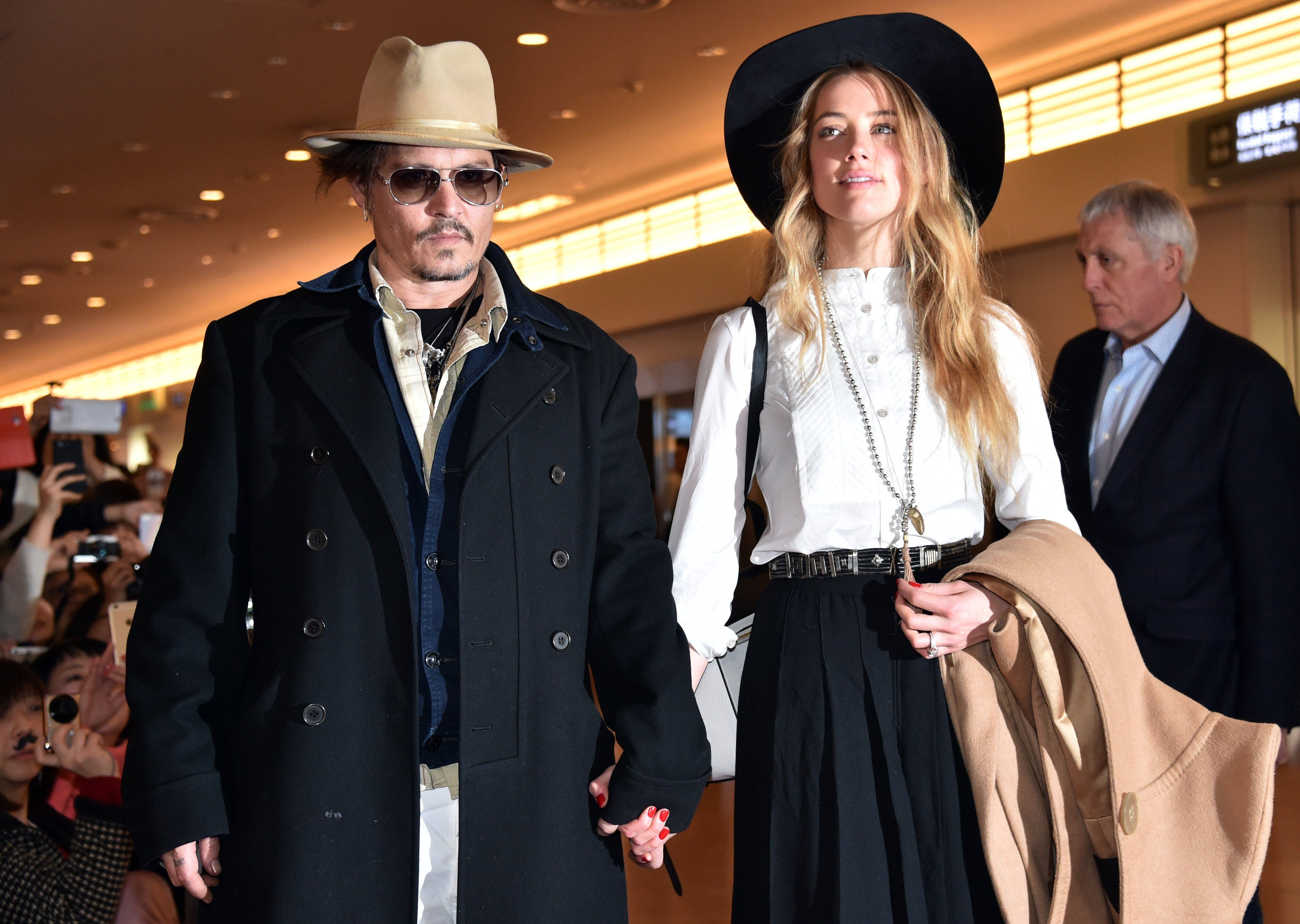 This file photo taken on January 26, 2015 shows US actor Johnny Depp (L) accompanied by his wife, US actress and model Amber Heard (R) after their arrival at Tokyo International Airport. (AFP)
