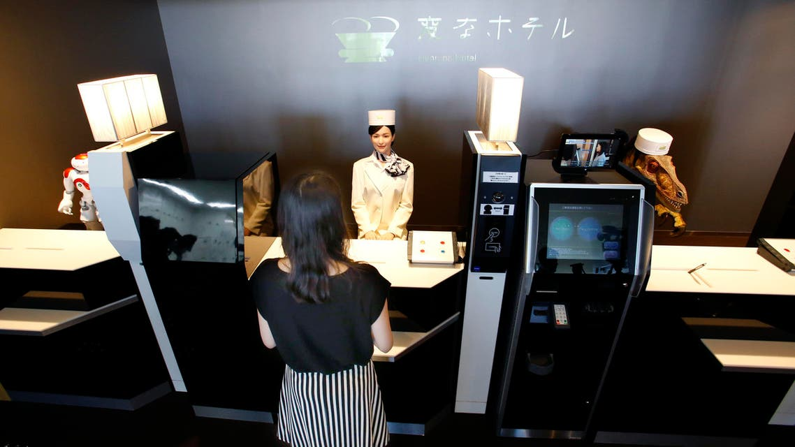 A receptionist robot, top center, accompanied by two other robots, greets a hotel employee demonstrating how to check in the new hotel, aptly called Henn na Hotel or Weird Hotel, in Sasebo, southwestern Japan, Wednesday, July 15, 2015
