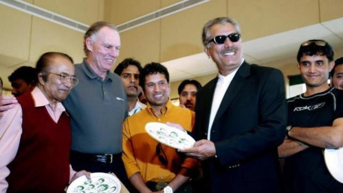 Former Pakistani cricketer Zaheer Abbas (2nd R) displays a plate carrying portraits of Pakistan's twelve great cricketers. Reuters
