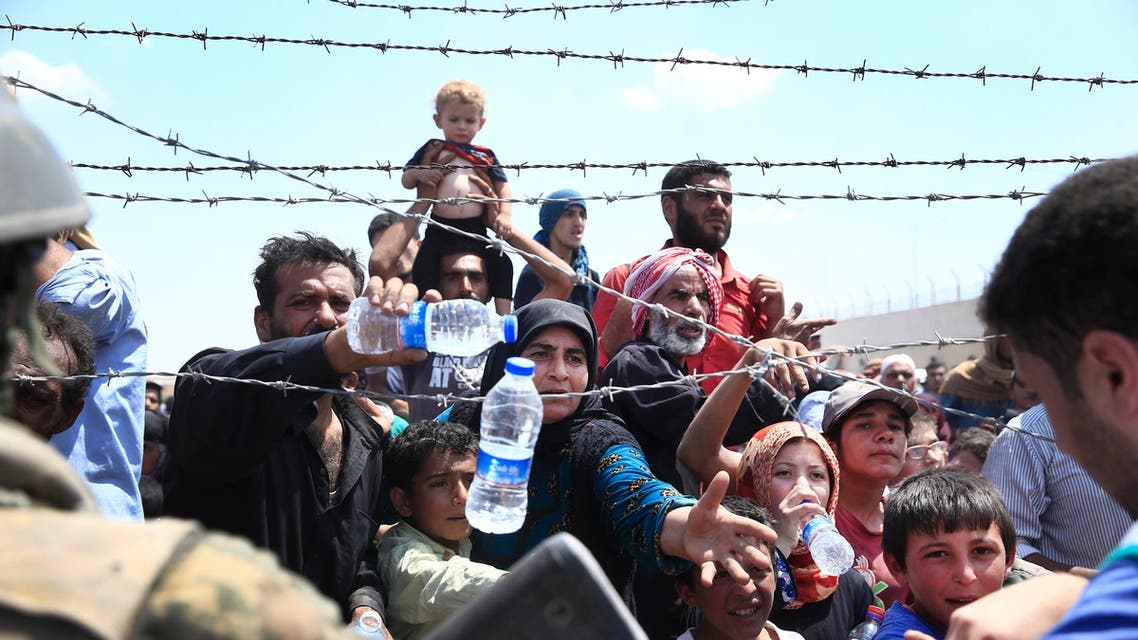 Syrian refugees receive water while they mass at the Turkish border as they flee intense fighting in northern Syria between Kurdish fighters and Islamic State militants in Akcakale, southeastern Turkey, Monday, June 15, 2015. AP