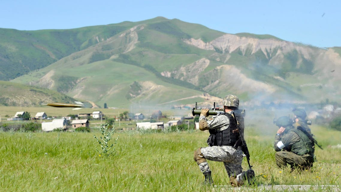 A Kyrgyz soldier fires a grenade from a grenade launcher, as Russian soldiers watch during joint Kyrgyz-Russian paratroopers exercise at the Ala-Too military base near Kyrgyz capital of Bishkek on Thursday, May 28, 2015. (AP)