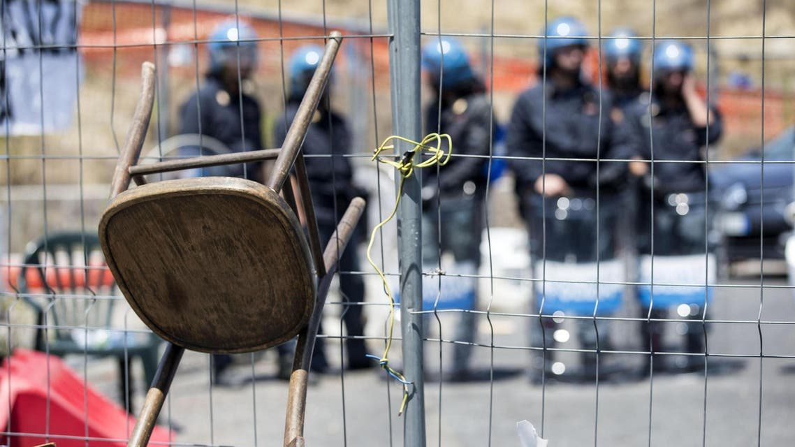Italian policemen in riot gear stand as residents and far right demonstrators protest against a migrants' arrival in the area in Rome, Friday, July 17, 2015. (Massimo Percossi/ANSA via AP)