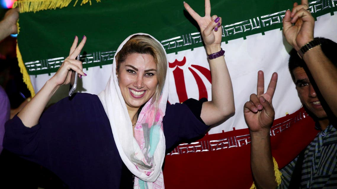 An Iranian woman shows the victory sign as people celebrate on a street following a landmark nuclear deal, in Tehran, Iran, Tuesday, July 14, 2015. Overcoming decades of hostility, Iran, the United States, and five other world powers struck a historic accord Tuesday to check Tehran's nuclear efforts short of building a bomb. The agreement could give Iran access to billions in frozen assets and oil revenue, stave off more U.S. military action in the Middle East and reshape the tumultuous region. (AP Photo/Ebrahim Noroozi)