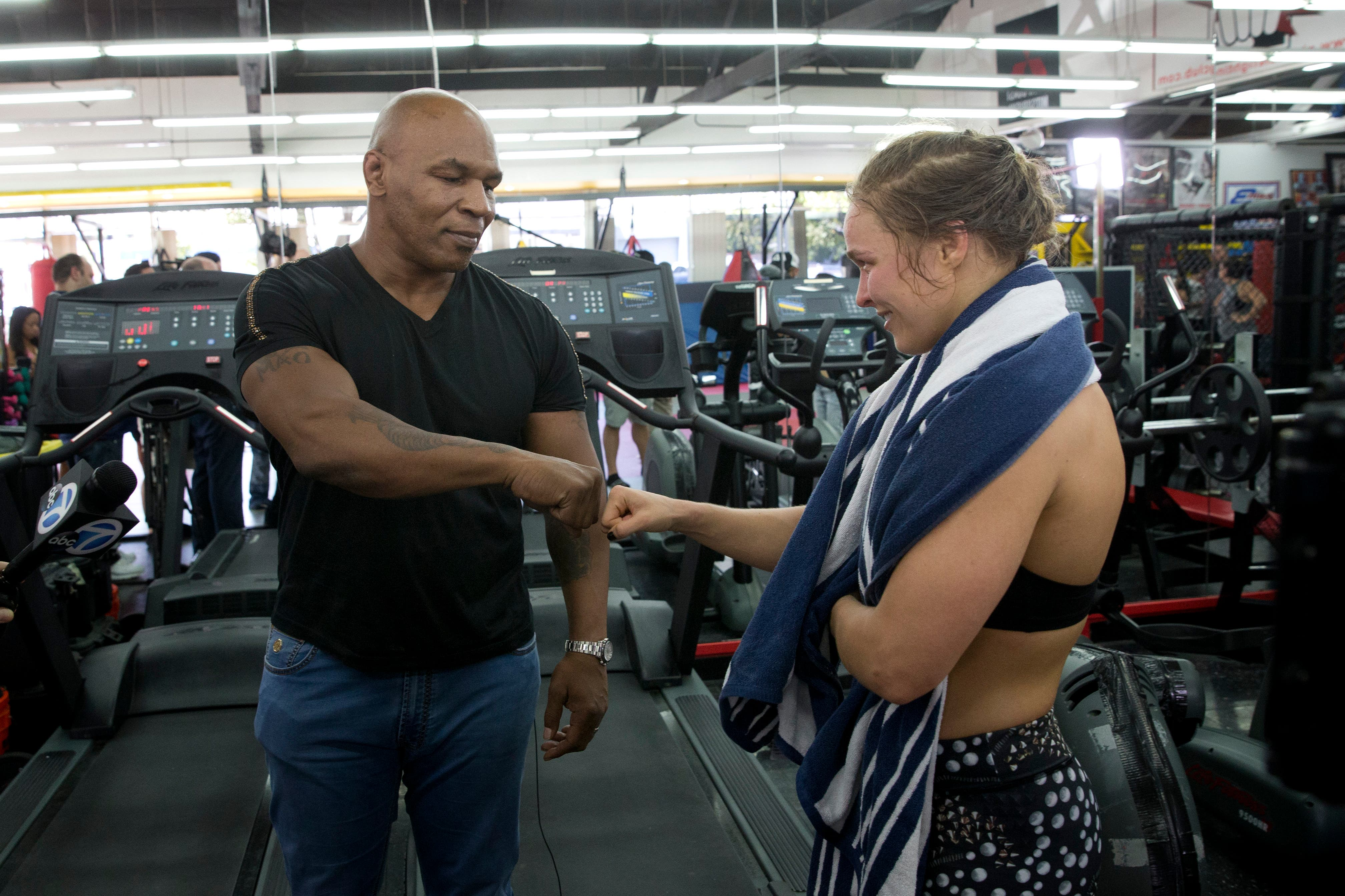 Mixed martial arts fighter Ronda Rousey, right, fist-bumps former boxer Mike Tyson after her workout at Glendale Fighting Club, Wednesday, July 15, 2015, in Glendale, Calif. Rousey, the UFC bantamweight champion, will return to the octagon against Brazil's unbeaten Bethe Correia at UFC 190 in Rio de Janeiro on Aug. 1. (AP Photo/Jae C. Hong)