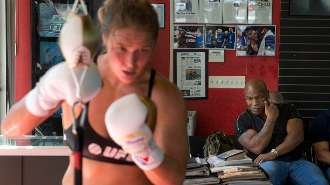 Former boxer Mike Tyson, right, watches as mixed martial arts fighter Ronda Rousey, foreground, works out at Glendale Fighting Club, Wednesday, July 15, 2015, in Glendale, Calif. Rousey, the UFC bantamweight champion, will return to the octagon against Brazil's unbeaten Bethe Correia at UFC 190 in Rio de Janeiro on Aug. 1. (AP Photo/Jae C. Hong)