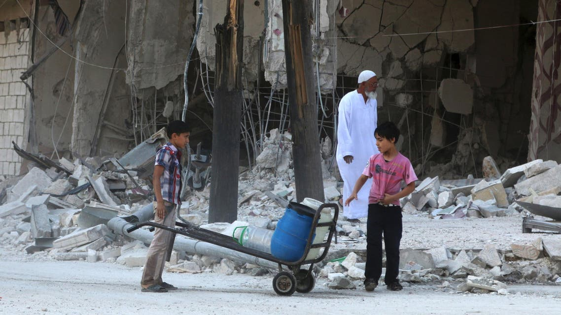 Children stand with water containers near a damaged building from what activists said was barrel bombs dropped by forces loyal to Syria's President Bashar Al-Assad in Aleppo's eastern district of Tariq al-Bab, Syria July 11, 2015. REUTERS/Abdalrhman Ismail