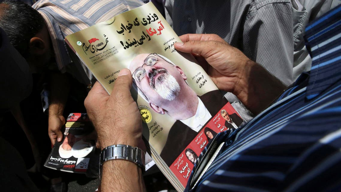 An Iranian worshipper holds May 2015 edition of a monthly magazine with portrait of Foreign Minister Mohammad Javad Zarif on Friday, July 17, 2015. (AP)
