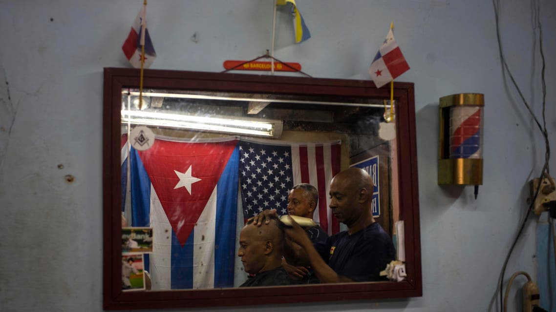 Eugenio Lafargue is reflected in a mirror as he cuts a client's hair inside his barbershop decorated with a Cuban and U.S. flag in Havana, Cuba, Saturday, July 18, 2015. Washington and Havana plan to officially restore diplomatic relations on Monday with the reopening of their embassies. (AP Photo/Ramon Espinosa)