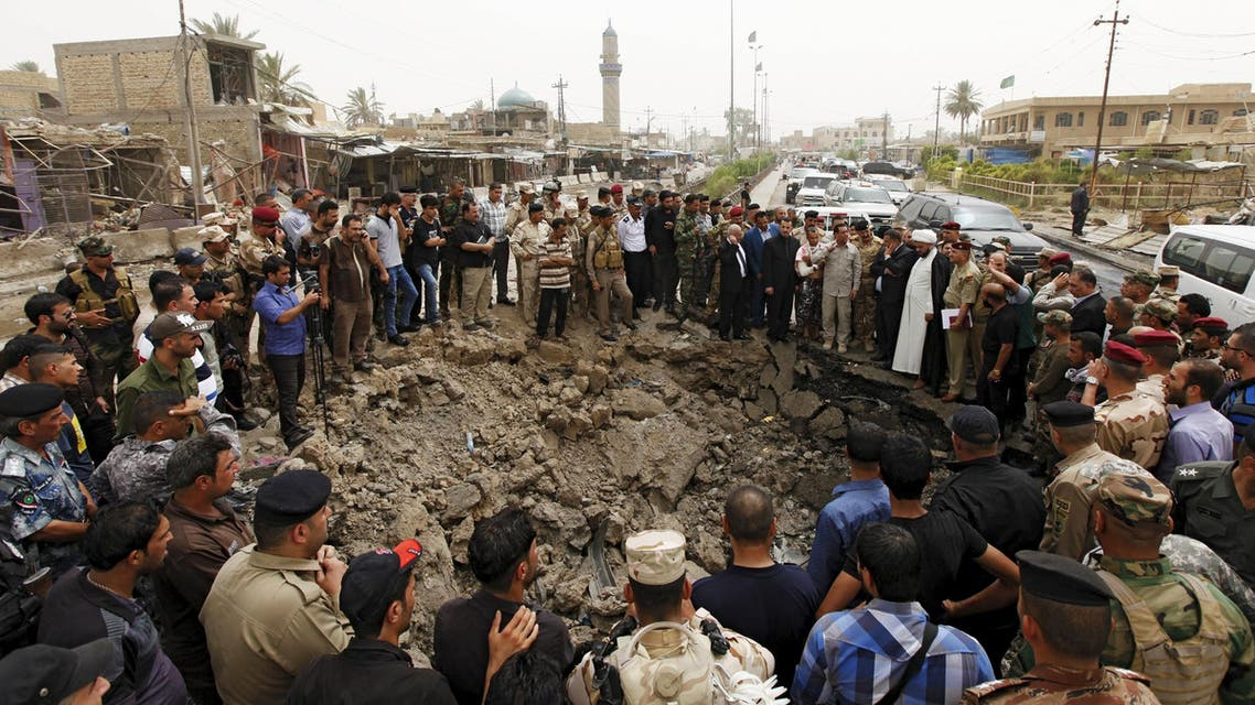 Residents and Iraqi security forces gather around a hole caused by a suicide car attack at a market in Khan Bani Saad, northeast of Baghdad. (Reuters)