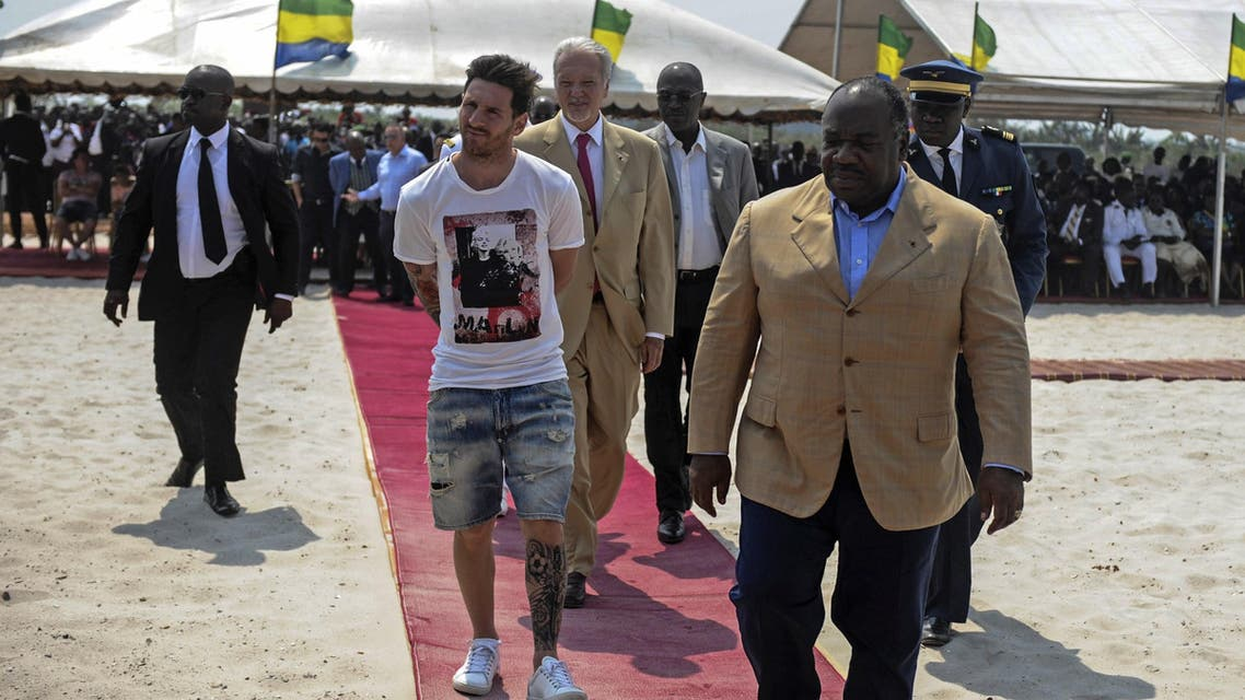 Argentinian soccer player and four-time FIFA Ballon d'Or winner Lionel Messi (C) is given a tour during the start of construction of the Port-Gentil Stadium by the President of Gabon, Ali Bongo Ondimba (R) in the Ntchengue district of Port-Gentil on July 18, 2015. AFP