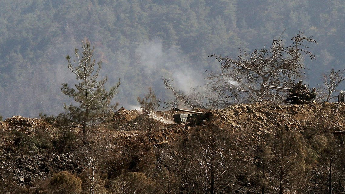 In this photo taken Thursday, March 27, 2014, Syrian government artillery forces fire towards rebels' position during clashes in Misherfeh town in the province of Latakia, Syria.