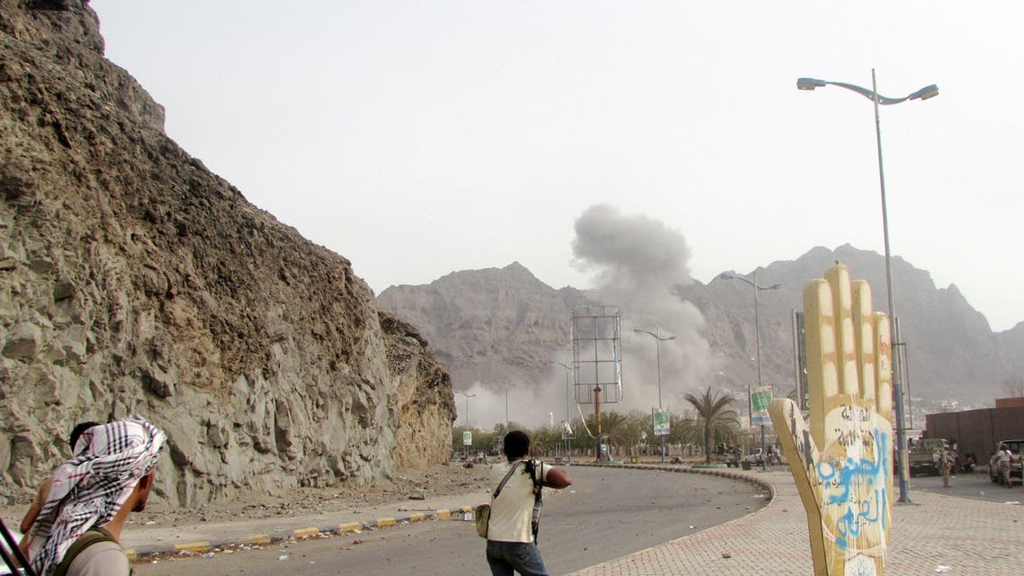 Southern Resistance fighters look as smoke rises from the site of a Saudi-led air strike on a position of Houthi fighters in Yemen's southern port city of Aden. (Reuters)