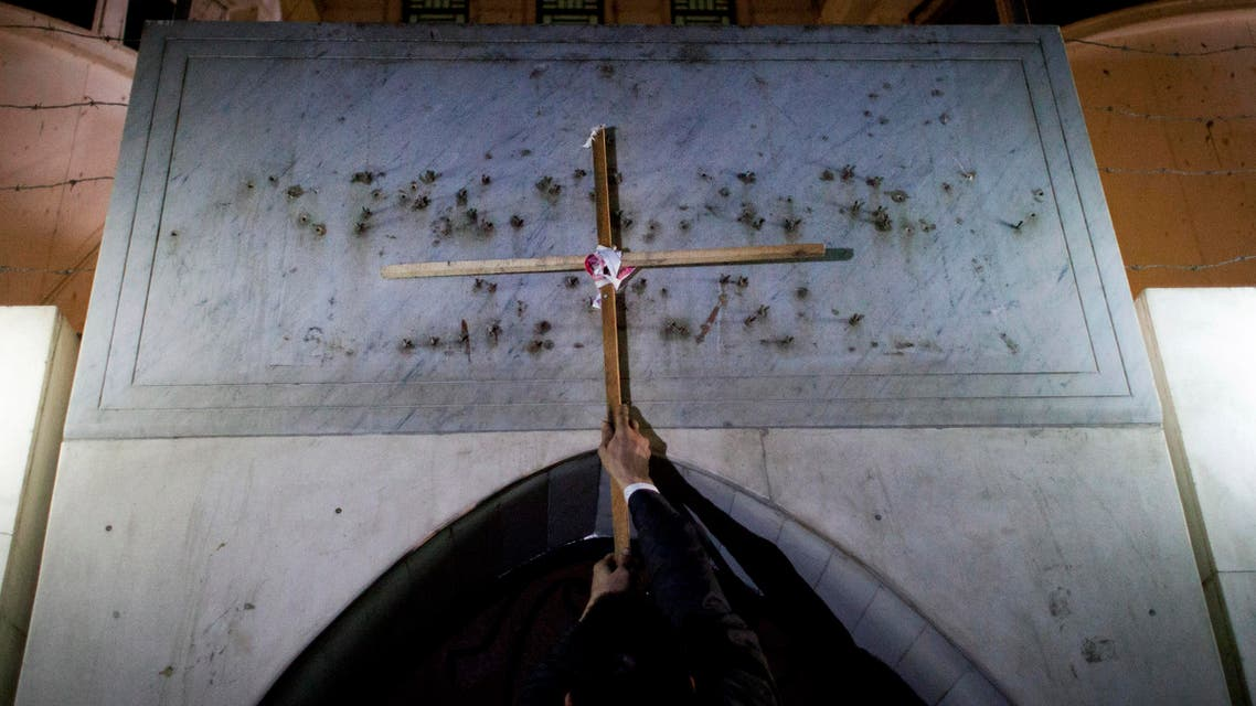 An Egyptian protester places a wooden cross at the entrance of the Libyan embassy AP