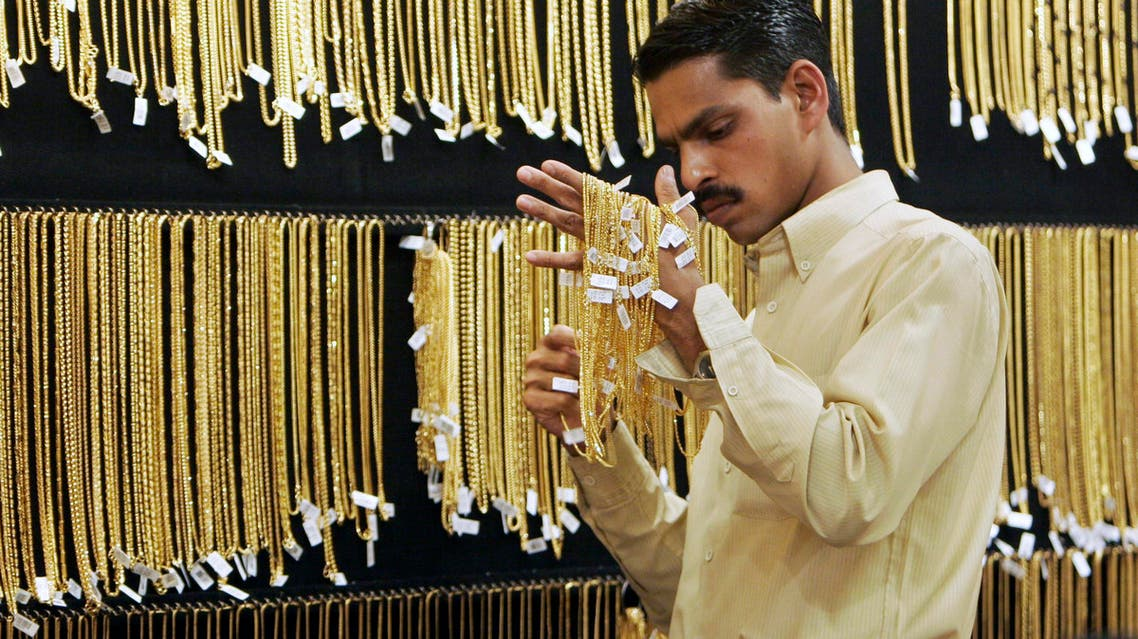 A salesperson arranges the gold chains at a jewelry store in Bangalore, India, Friday, March 14, 2008. Gold zoomed past all previous records to set at new peak of Rupees 13,200 or US$ 325 per ten grams on the bullion market Friday. (AP Photo/Aijaz Rahi)