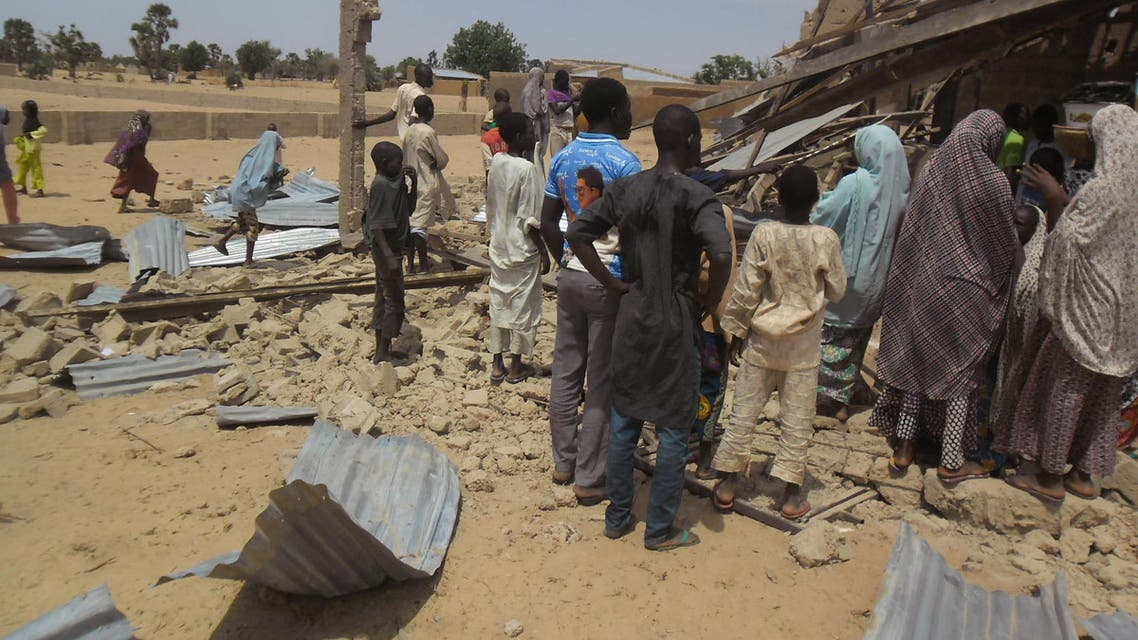 People gather around the Redeemed Christian Church of God, after a bomb blast in Potiskum, Nigeria, Sunday, July 5, 2015. A woman suicide bomber blew up in the midst of a crowded evangelical Christian church service in northeast Nigeria on Sunday and killed at least five people, witnesses said. (AP Photo/Adamu Adamu Damaturu)