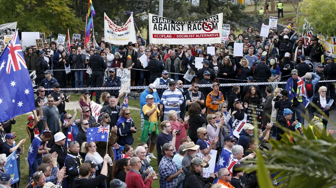 """Opposing protest groups, from the """"Reclaim Australia"""" anti-islam group and those calling for an end to racism are separated by a police line in Brisbane"""