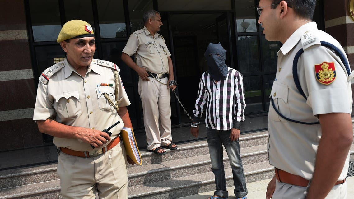 Indian police officers escort Ravinder Kumar, who is accused of murdering and sexual assaulting a six-year-old girl, at a police station in New Delhi on July 20, 2015. Indian police said July 20 they are investigating whether a man arrested for the murder and sexual assault of a six-year-old girl may have been a serial child killer after he confessed to 14 more crimes. AFP PHOTO / SAJJAD HUSSAIN
