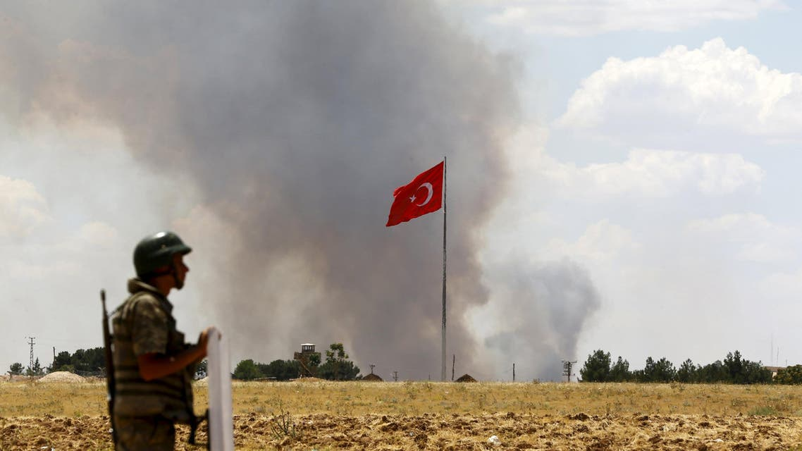 A Turkish soldier stands guard while smoke rises in the Syrian town of Kobani as it is seen from the Turkish border town of Suruc in Sanliurfa province. (File: Reuters)