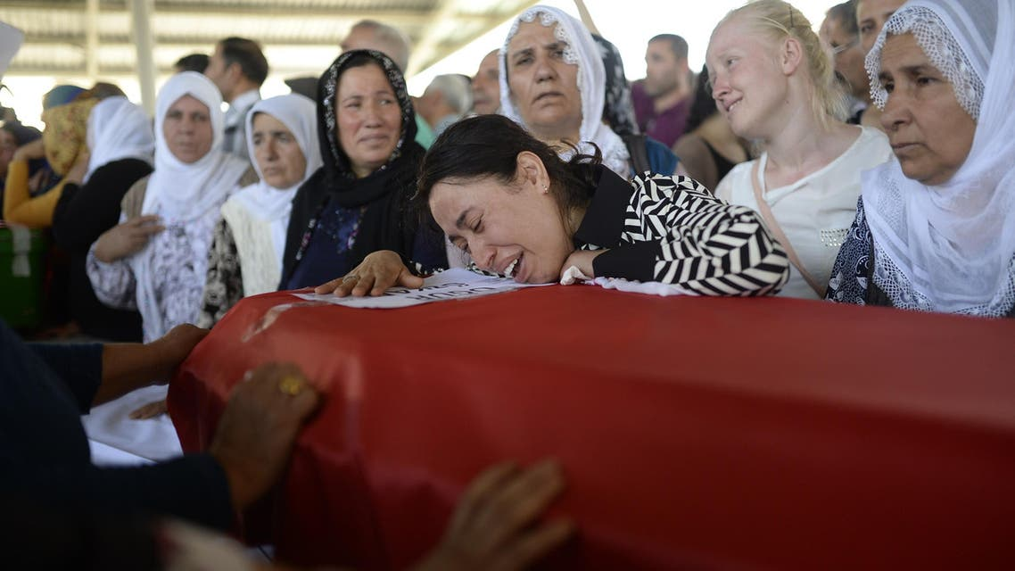 A woman reacts over a coffin as people mourn relatives in Gaziantep on July 21, 2015, AFP