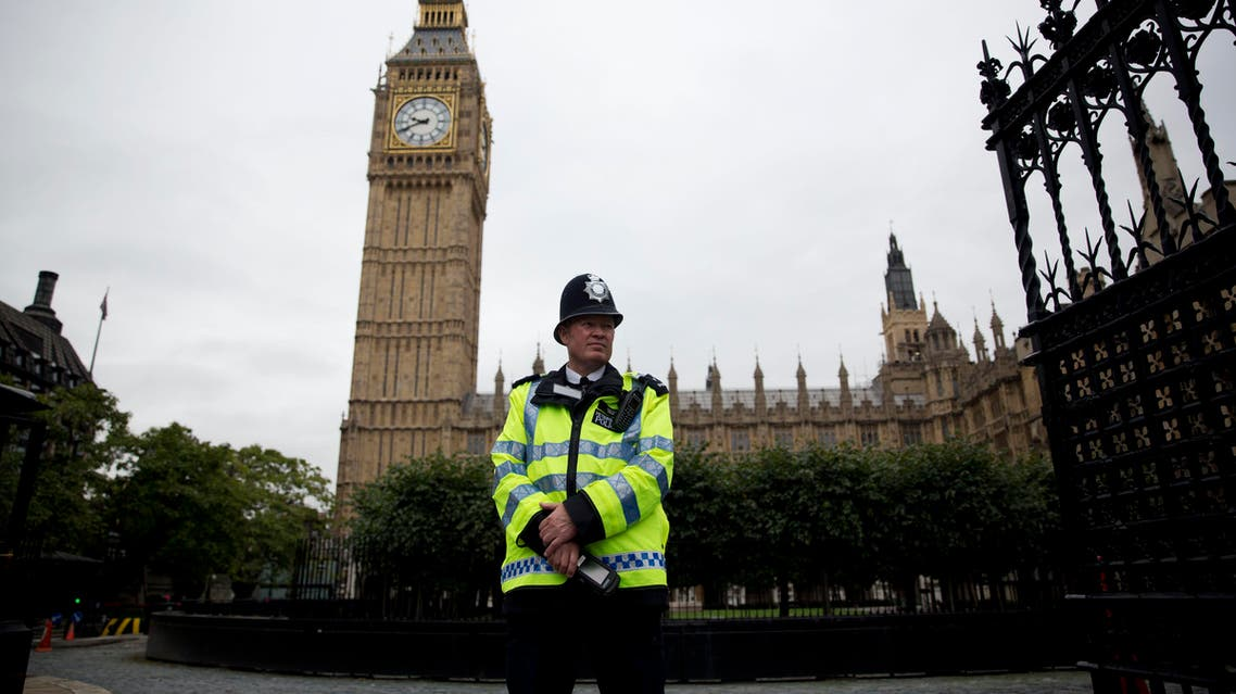 a British police officer stands guard outside the Houses of Parliament in London. The military-style daylight attack on the streets of Paris on Wednesday, Jan. 7, 2015. AP