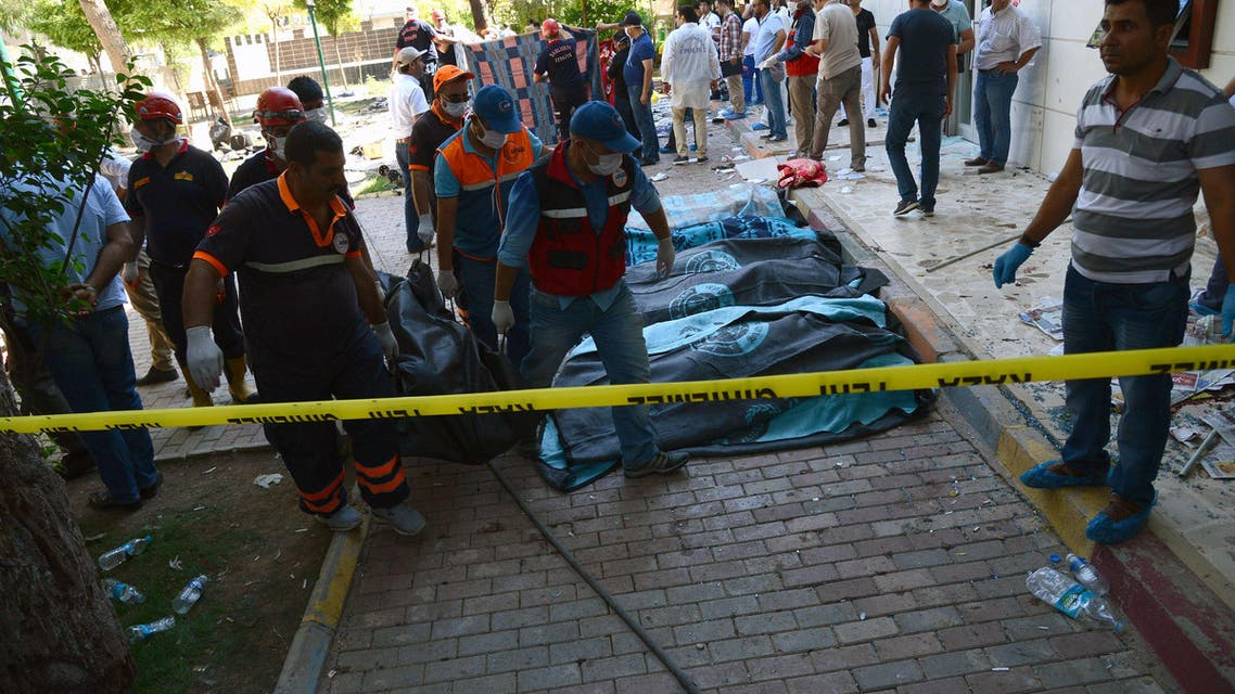 Turkish officials carry the bodies of victims on July 20, 2015