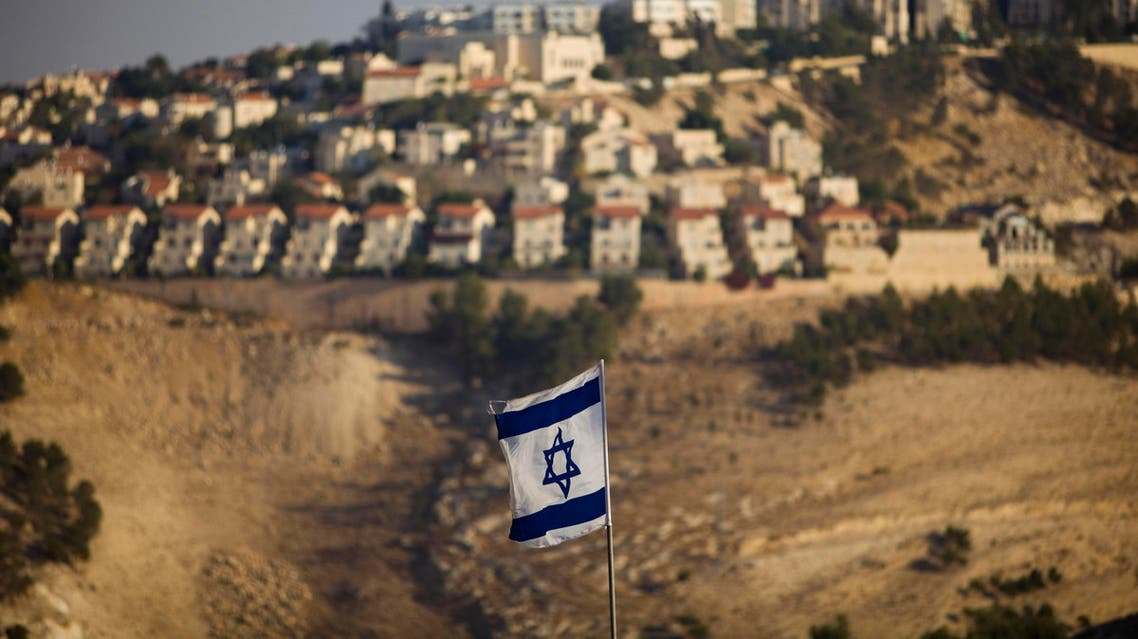 In this Monday, Sept. 7, 2009 file photo, an Israeli flag is seen in front of the West Bank Jewish settlement of Maaleh Adumim, on the outskirts of Jerusalem. AP
