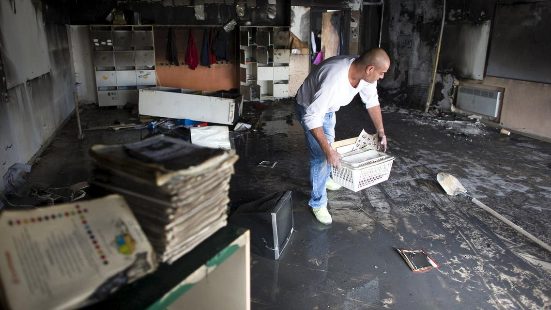 A worker cleans up in a torched classroom in an Arab-Jewish school in Jerusalem, in this November 30, 2014 file picture. An Israeli court jailed two brothers from a far-right Jewish group on July 22, 2015 for the arson attack on the Jerusalem school that had been a rare symbol of co-existence in the riven city. REUTERS/Ronen Zvulun/Files