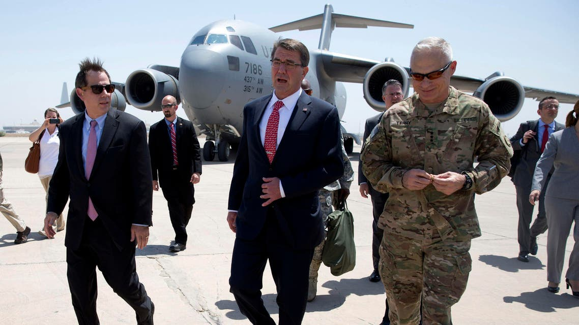 U.S. Defense Secretary Ash Carter, center, is greeted by U.S. Ambassador to Iraq Stu Jones, left, and Army Lt. Gen. James Terry, right, as he arrives at Baghdad International Airport in Baghdad, Iraq, Thursday, July 23, 2015.