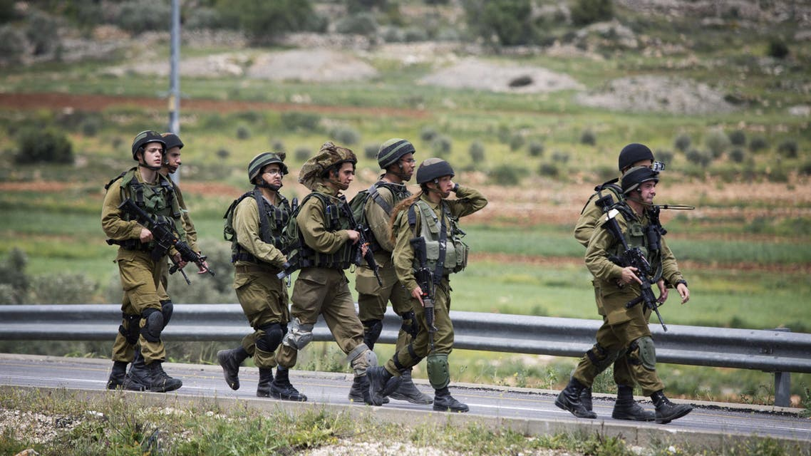 Israeli soldiers patrol after a stabbing attack by a Palestinian man near the village of Sinjil, between the cities of Ramallah and Nablus, Wednesday, April 8, 2015. (AP)