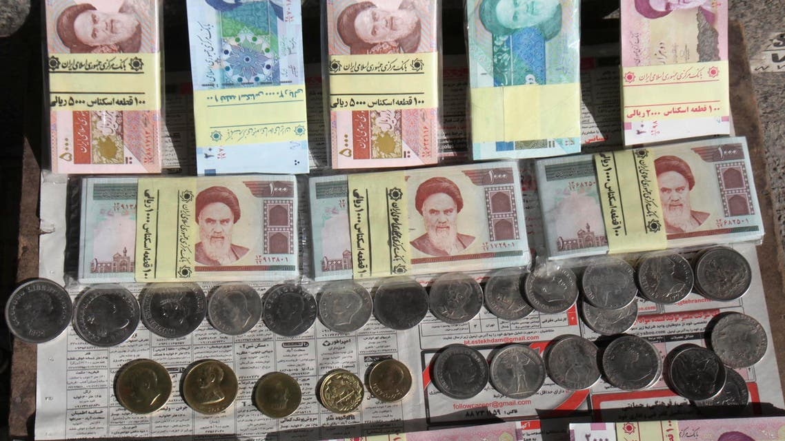 Iranian banknotes and foreign coins are displayed by a vendor on a side walk of the Ferdowsi Street in Tehran, Iran, Wednesday, Jan. 23, 2013.  (AP)