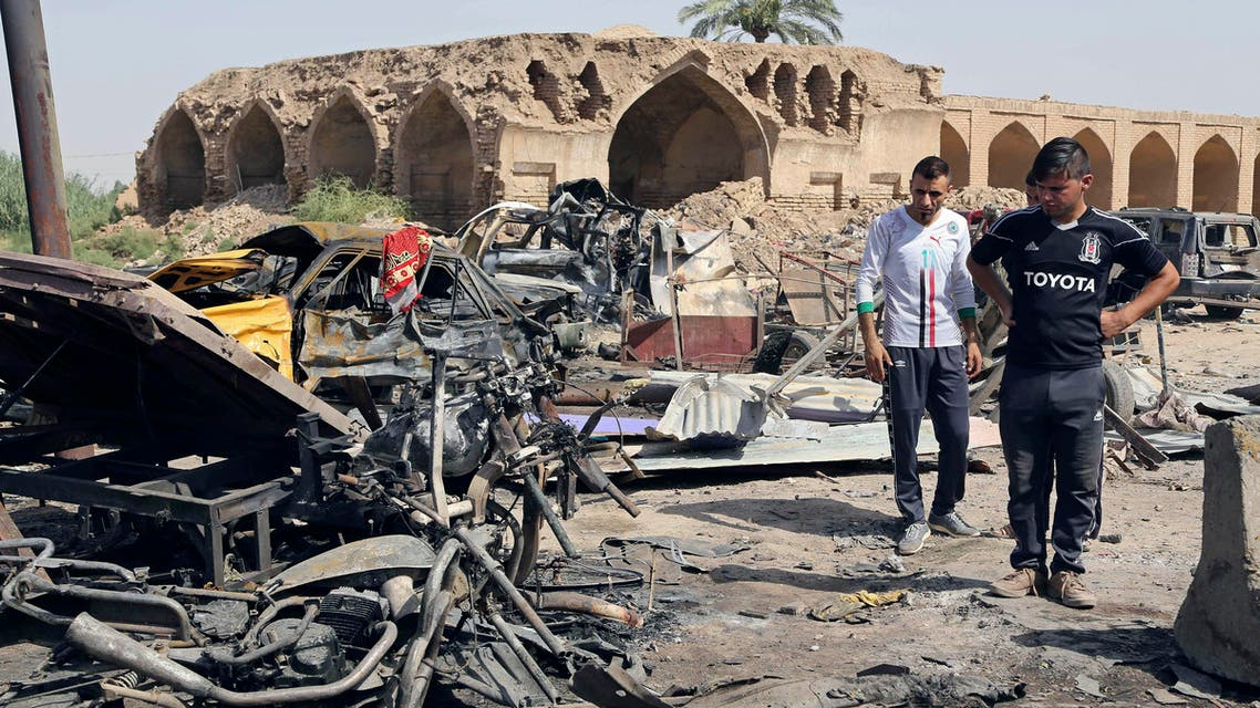 Civilians inspect the scene of a deadly Friday night suicide car bombing at a busy market in Khan Beni Saad, about 20 miles (30 kilometers) northeast of Baghdad, Iraq, Saturday, July 18, 2015. AP